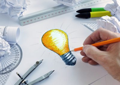 Designer drawing a light bulb, concept for brainstorming and ins